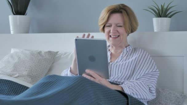 Online Video Chat na tabletu unavené staré starší žena v posteli
