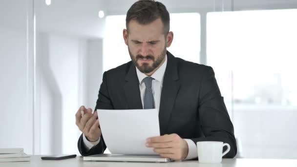 Naštvaný podnikatel reaguje na ztrátu při čtení dokumentů
