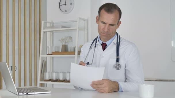 Arzt liest Dokumente in Klinik, Papierkram