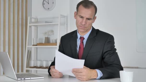 Rozzlobený středního věku podnikatel reakce na ztrátu při čtení dokumentů