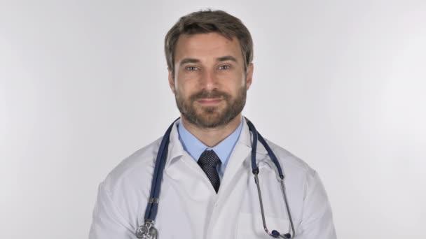 Unavený lékař při pohledu na fotoaparát ve studiu na bílém pozadí