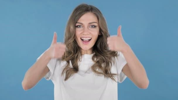 Mladá dívka směřují palec nahoru izolované na modrém pozadí