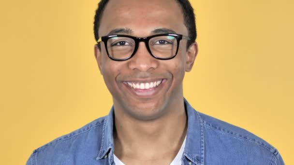 Zblízka s úsměvem africké muž v brýlích, samostatný na žlutém podkladu