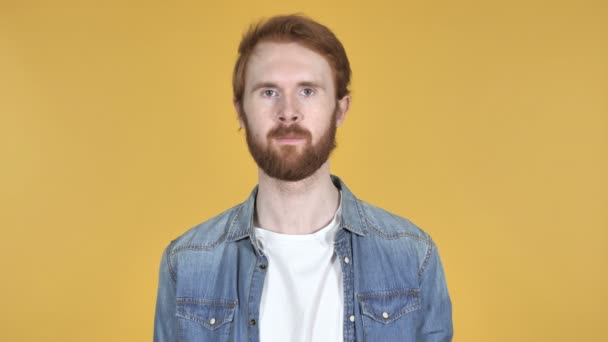 Redhead Man Looking at Camera Isolated on Yellow Background