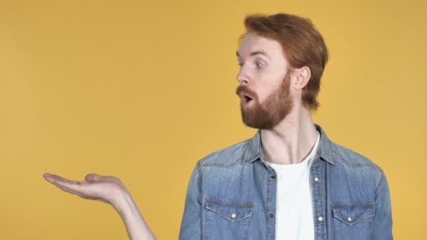 rothaariger Mann zeigt Produkt seitlich, gelber Hintergrund