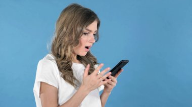 Young Girl Excited for Success while Using Smartphone Isolated on Blue Background