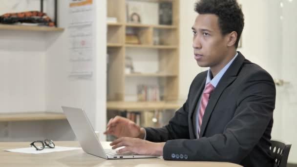 Müder afrikanischer Geschäftsmann mit Nackenschmerzen arbeitet am Laptop