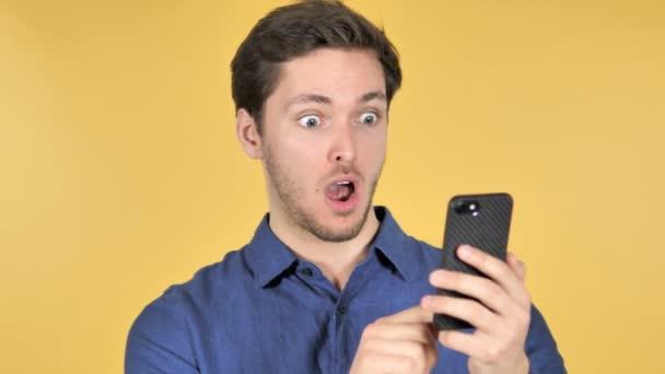 wow, überrascht lässiger junger Mann mit Smartphone auf gelbem Hintergrund