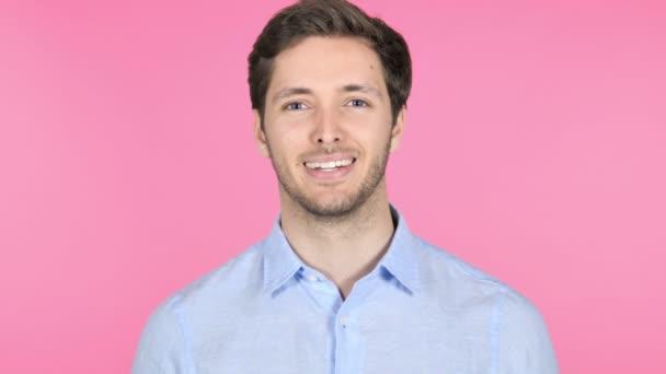 Usmívající se mladý muž izolovaný na růžovém pozadí
