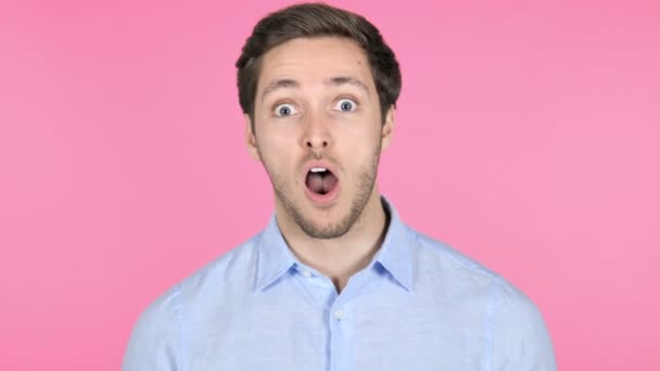 Surprised Young Man Wondering on Pink Background