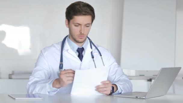 Mladý lékař čtení lékařské zprávy, provedení papírování