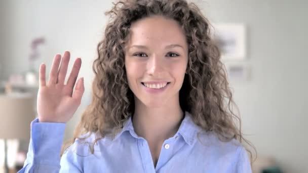 hallo, Frau mit lockigem Haar winkt zur Begrüßung