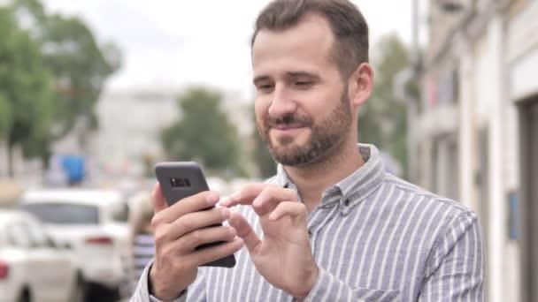 Venkovný vousatý muž používající smartphone