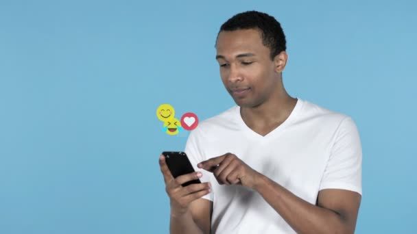 African Man Using Smartphone Isolated on Blue Background, Flying Smileys, Emojis and Likes
