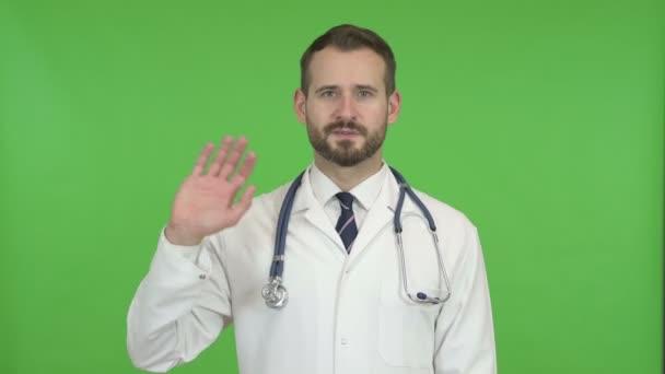 schöner Arzt winkt und spricht gegen Chroma-Schlüssel