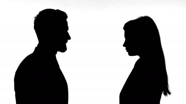 Silhouette delluomo schiaffeggiante donna contro sfondo bianco