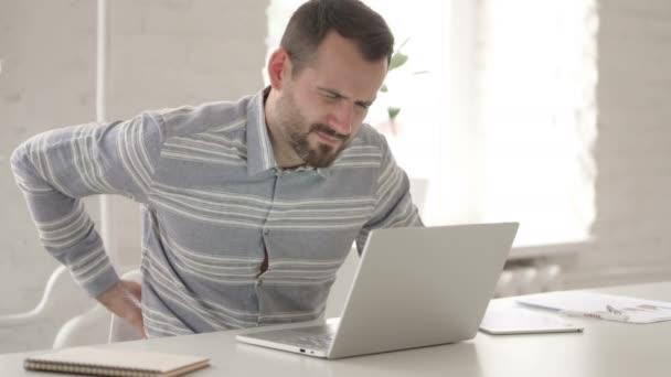 Dospělý muž s bolestí zad pomocí přenosného počítače