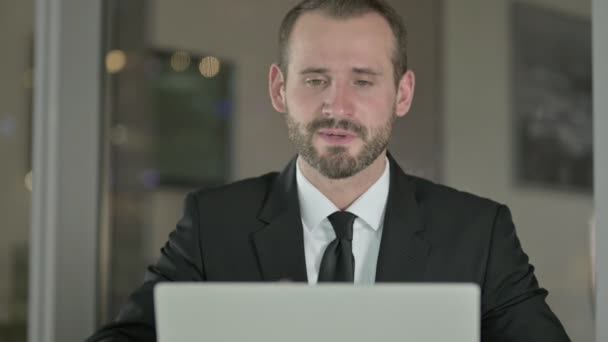 Großaufnahme eines ehrgeizigen Geschäftsmannes, der nachts am Laptop Videochats führt