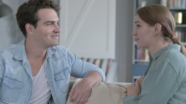 Vidám pár Mosolyog és beszél Ül a kanapén