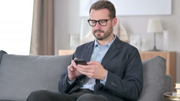 Young Businessman Celebrating Success on Smartphone at Home