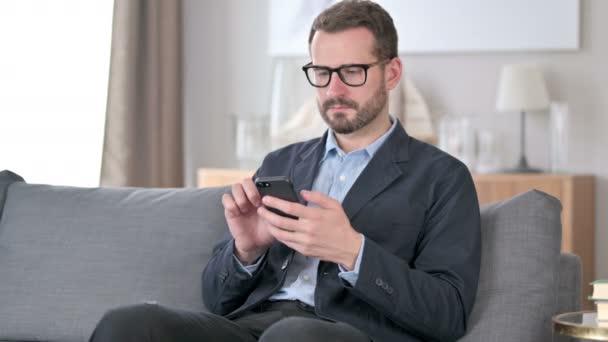 Atraktivní mladý podnikatel používající Smartphone doma