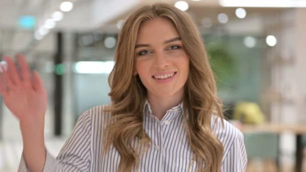 Porträt einer fröhlichen Geschäftsfrau, die in die Kamera winkt