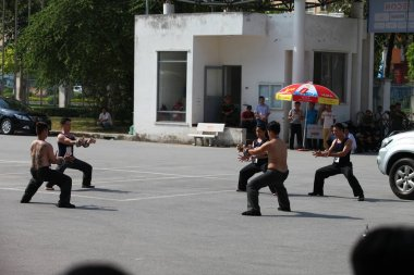 Hanoi, Vietnam - Aug 9, 2015: Vietnamese pugilists in traditional costume doing a performance of martial arts on a public and free entrance event in Hanoi capital.