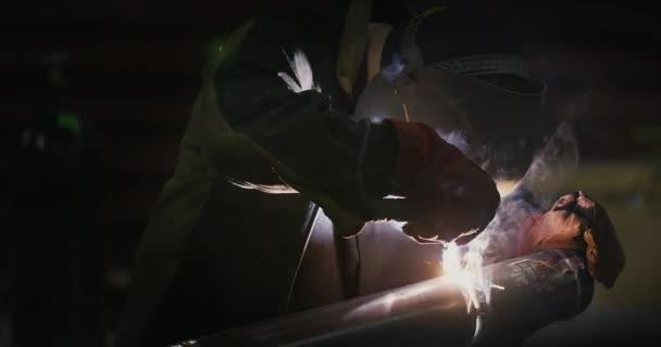 Svářečka svářecí masky, v pracovních šatech v továrně, svary potrubí v prostoru továrny. Svářečka. Průmysl. Práce v továrně. Svařování potrubí. Elektroda. Tání. Svářečské práce. Pomalý pohyb. S lidmi.