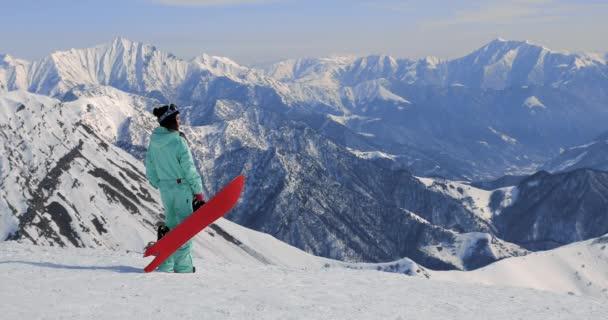 pohled na samičí snowboardista se snowboardu v jedné ruce a požívající hory
