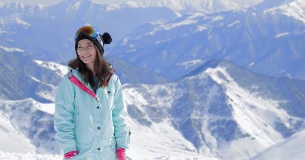 glückliche Snowboarderin mit Snowboard lächelnd auf der Skihang-Kulisse