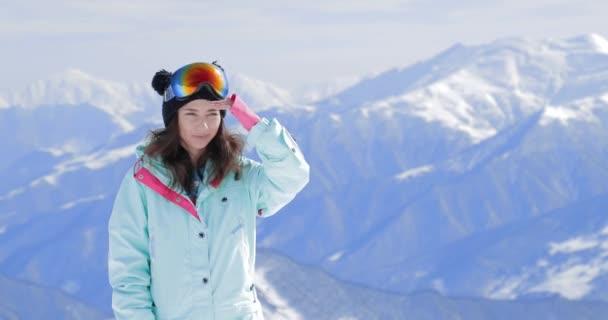 Šťastný dívčí snowboardista se snowboardu s úsměvem na pozadí lyžařského svahu