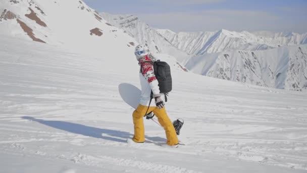 Záběr muže, který drží na rukou snowboardista.