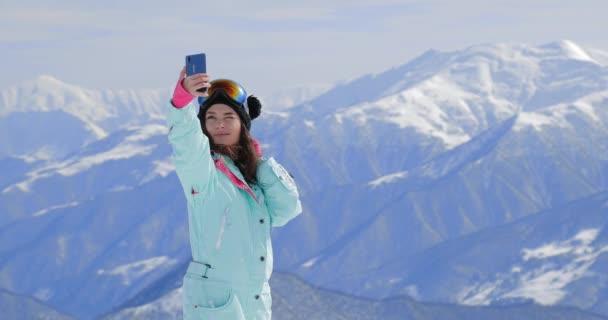Snowboarderin fotografiert mit ihrem Smartphone in den Bergen