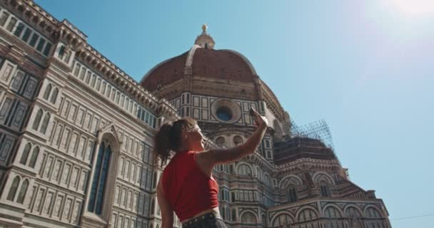 Woman taking selfie on background of Santa Maria cathedral