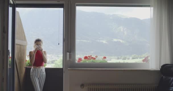 Dívka s kávou si v okně vychutná krajinu
