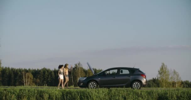 Nervous young girls standing near with smoking car on the road