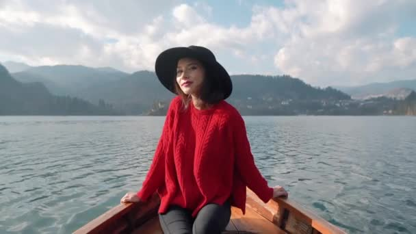 Happy asian woman relaxing in boat on the beautiful summer lake during her vacation. Pretty young girl sitting in boat and looking for the inspiration at background of the Alph mountain view.