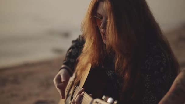 Red-haired hipster girl in beautiful sunglasses plays the guitar. Pretty female sings a song on sunset background. Vacation at the sea. Atmosphere of love. Self isolation, travel concept.