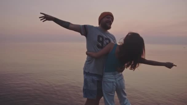 Beautiful couple hugs and kisses standing in the middle of the sea. Hipster guy and girl enjoy a vacation on sunset background. Sun over the amazing pink sea. Concept of isolation together