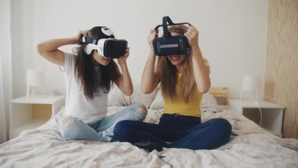 Pretty girls in VR in helmets at home. Two women put on virtual reality headsets while sitting on bed, surprising by the image they see. 3D technology. concept of virtual reality, Gaming, friendship.