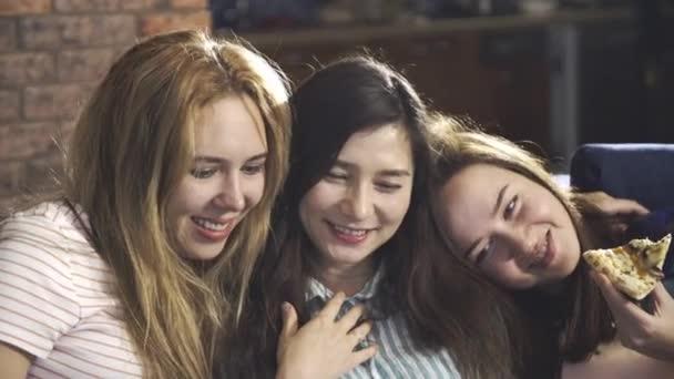 Multiracionális tinédzserek ülnek éjjel a nappaliban, és filmet vagy TV-t néznek. Három barátnő összekapcsolja és megvitatja az információt a laptop képernyőjén. A legjobb barátok mosolyognak és nevetnek egymással..