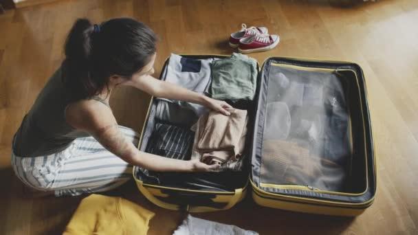 Elképzelése utazás, kaland, utazás. Fiatal lány készül az utazásra, ruhákat pakol egy sárga bőröndbe. egy gyönyörű tetovált hölgy összegyűjti a legszükségesebb dolgokat az utazás előtt.