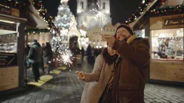 Milenci cestující do Evropy na vrcholu vánočních svátků. Miláčkové se líbají v centru starého města. Romantický pár v lásce objímání a pálení jiskry na slavnostní pouliční veletrh.