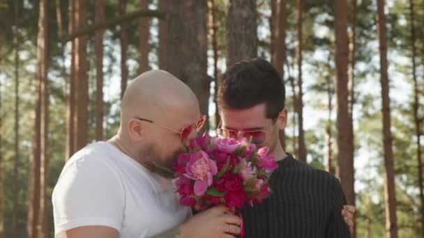 Egy homokos pár portréja, akik boldogok együtt. Meleg esküvői koncepció. Két férfi virágcsokorral, gyűrűvel az ujján mosollyal és öleléssel. Kapcsolati célok. LMBTQI, Pride Event, LMBT Pride Hónap, Meleg Büszkeség Szimbólum