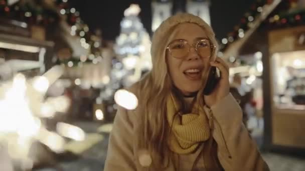 Adorable girl talking on the phone surrounded with lights and sparklers near the fair in the centre of european city. Young blond woman congratulating friends with Christmas from Prague.