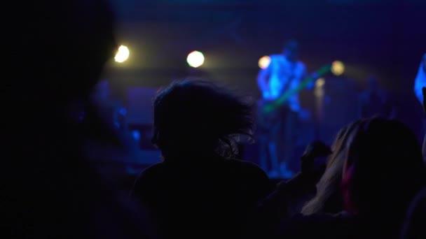 Živé koncertní vystoupení v klubu plném lidí zvedajících ruce do vzduchu. Koncept paření a zábavy. Hip-hop hvězda vystupující na jevišti před fanoušky. Noční koncert hudby.