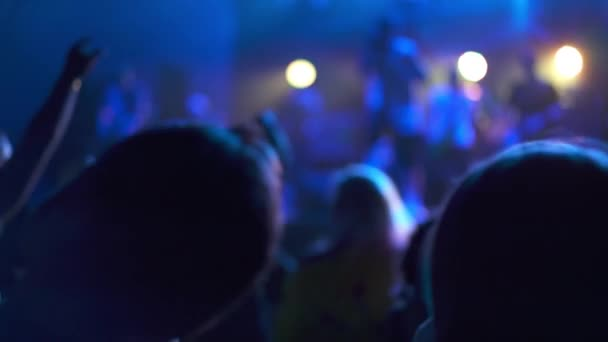 Concept of the party and entertainment. The crowd at music concert, the audience raising their hands up. Gig in a night club, people having fun and enjoying dancing on the dance floor. Rock music