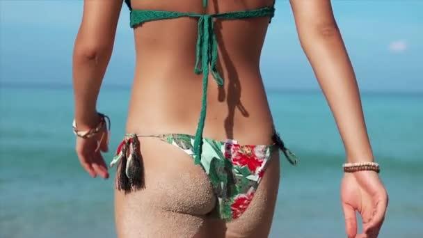Visszapillantás a sekély vízbe lépő nőre. Gyönyörű fit lány sétál a tengeren a strandról, hogy nyaralni a csodálatos trópusi tengerparton.