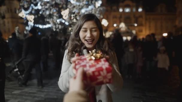 Dárek pro ženu na Štědrý večer na Staroměstském náměstí, pohled první osoby. Láska, rodina, Vánoce, Nový rok, sváteční koncept. Natočeno na RED kameře, 10 bitový clolor