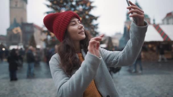 Pěkná bílá žena, která bere selfie po telefonu na vánoční pozadí. Cestování, štěstí, Vánoce, prázdninový koncept. Natočeno na RED kameře, 10 bitový clolor